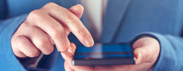 Image of hands using a mobile phone used in article about facebook advertising